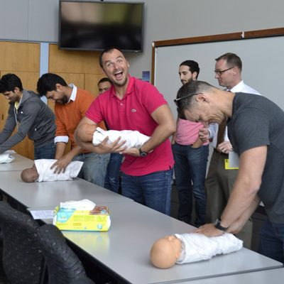 Shows new dads class participants learning to swaddle with baby dolls