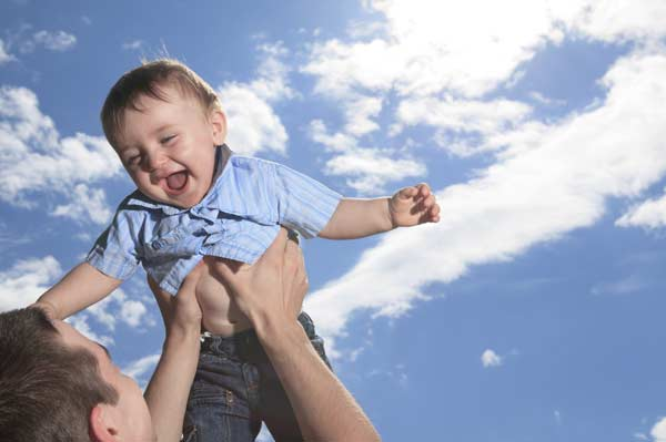 Dad holds laughing baby up in the air, against the background of a blue sky